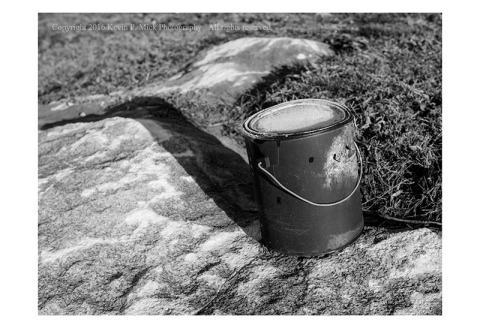 BW photograph of a long abandoned, rusty, paint can sitting on a rock