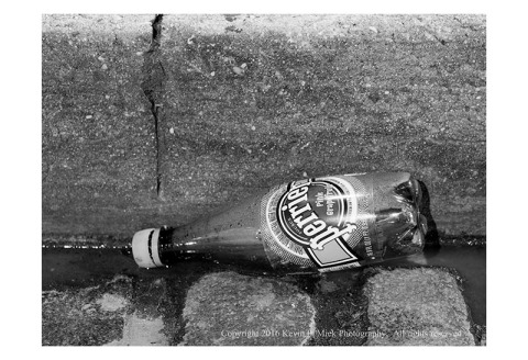 BW photograph of a Perrier bottle lying in the gutter
