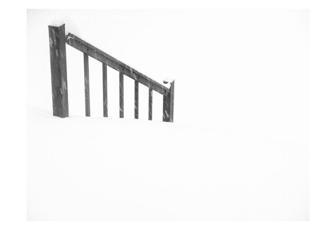 BW photograph of a black porch rail in a snowstorm
