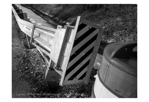 BW photograph of a bent guardrail aloing a highway