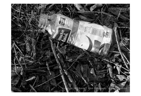 BW photograph of a thrown away Minute Maid juice bottle lying in a pile of sticks