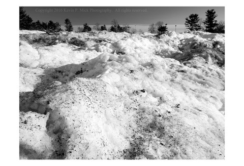 BW photograph of a large snowbank of piled snow in a parking lot