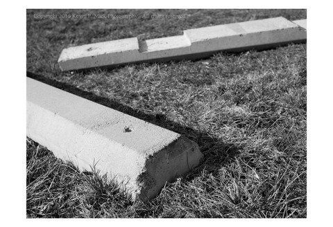 BW photograph of two concrete bumpers that have been moved from a parking lot.