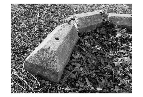 BW photograph of a concrete bumper that has been moved and has broken into three pieces.