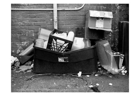 BW photograph of a plastic bin brimming with throw away plastic, some cardboard boxes, and styrofoam peanuts