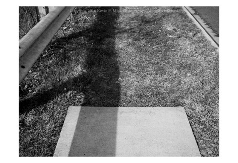 BW photograph of a sidewalk that ends in a strip of grass.