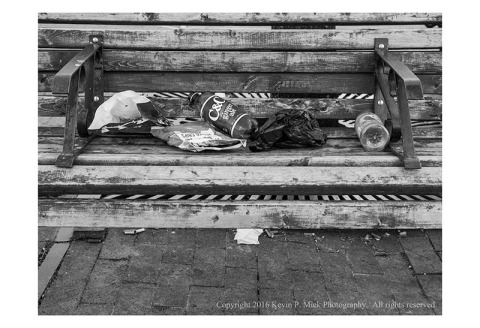 BW photograph of a bench with trash-plastic bags and bottles.