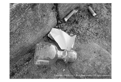 BW photograph of a small bottle and a gum wrapper lying in a gutter.