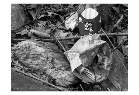 BW photograph of McDonalds trash lying in the woods.