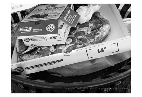 BW photograph of a pizza in a trashcan.