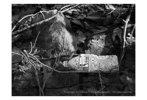 BW photograph of a plastic water bottle lying in a stream.
