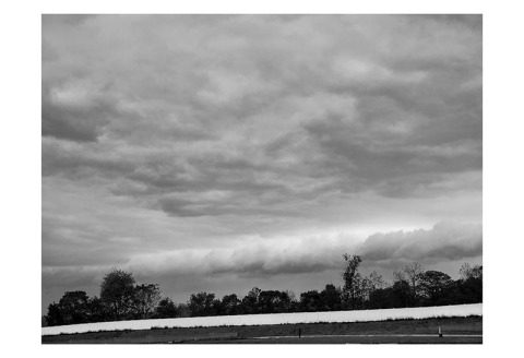 BW photograph of incoming rain clouds over a treeline.