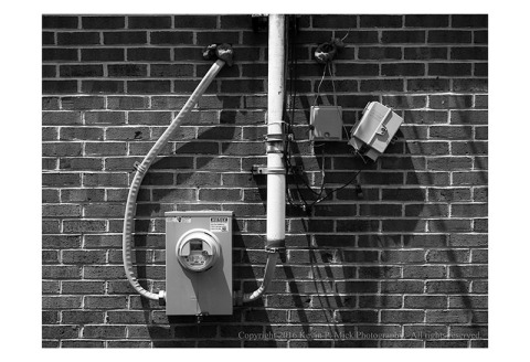 BW photograph of electrical conduits and meters in strong sunlight producing shadows.