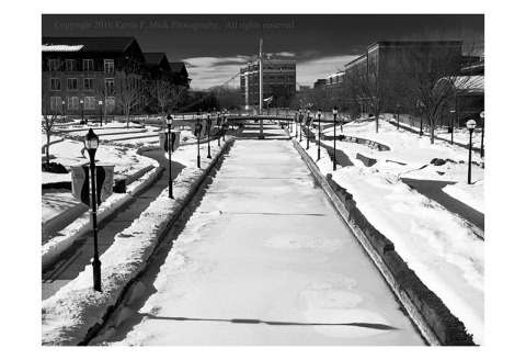 BW photograph of Carroll Creek in Frederick, Maryland, in winter, looking west.