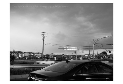 BW photograph of an approaching thunderstorm over a congested shopping area.