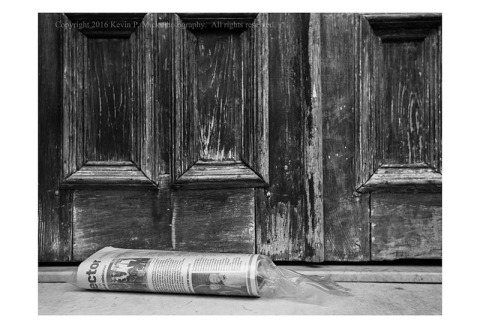 BW photograph of a plastic-sleeved newspaper laying on a marble stoop.