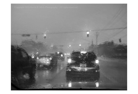 BW photograph of traffic stopped at a stoplight during a thunderstorm.