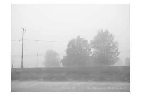 BW photograph looking outward from a vehicle at trees in the distance during a thunderstorm.