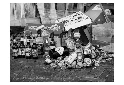 BW photograph of trash and garbage piled up on a sidewalk.