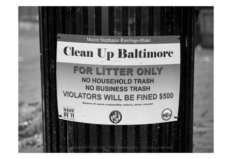 "BW photograph of a sign attached to a trash can advocating to ""Clean Up Baltimore""."