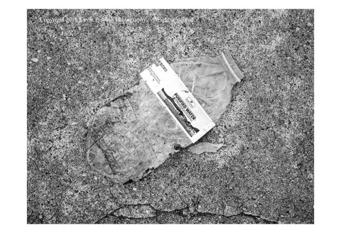 BW photograph of a crushed water bottle that, except for the white label, is virtually invisible against a sidewalk.