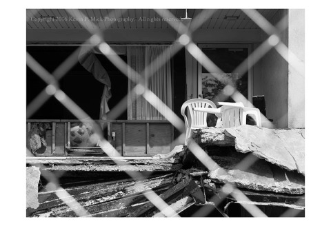 BW photograph of a room in a hotel being deconstructed as seen through a chain link fence.