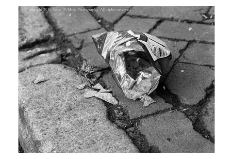BW photograph of discarded bag of chips spilling onto the sidewalk.