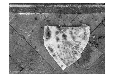 BW photograph of an overturned slice of pizza laying on the sidewalk.
