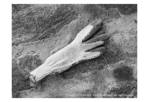 BW photograph of a lost glove laying on a cobblestone street.