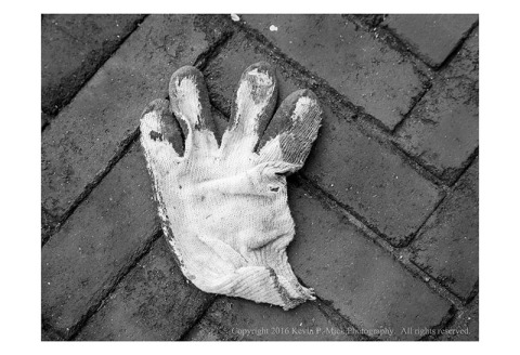 BW photograph of a lost glove laying on a brick sidewalk.