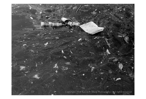 BW photograph of three plastic bottles, a styrofoam clamshell box, and other dietrius floating in the water.