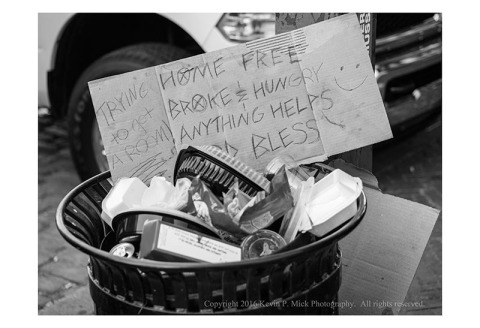 "BW photograph of a cardboard sign stating ""Home Free Broke & Hungry Anything Helps God Bless Trying to gt A Room"" in a trashcan."