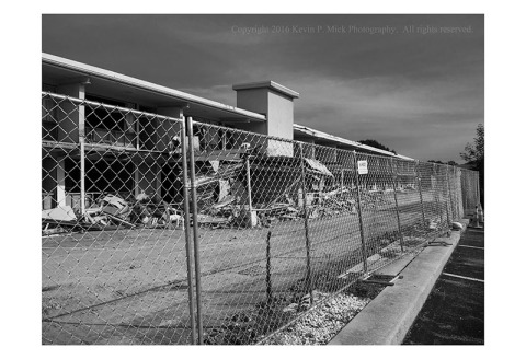 BW photograph of a motel being deconstructed as seen through a chain-link fence.