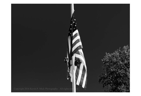 BW photograph of an American flag wrapped around its pole.
