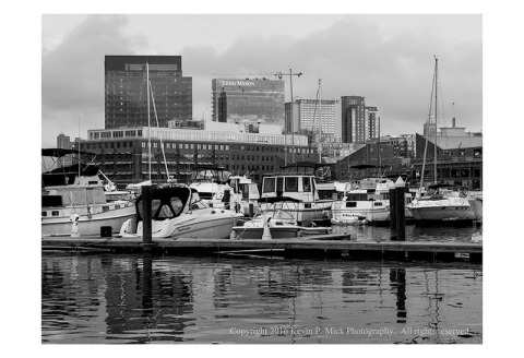 BW photograph of the sun rising onto Harbour East in Baltimore, Md.