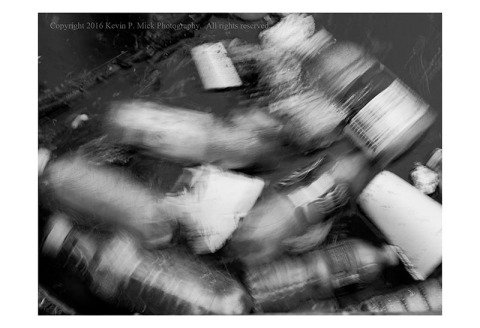 BW photograph of water bottles and styrofoam cups swirling in water.
