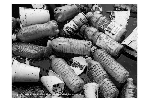 BW photography of plastic bottles ans styrofoam cups floating in the water.