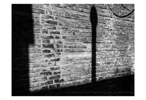 BW photograph of strong shadows against a brick wall.