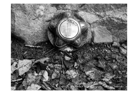 BW photograph of a lost lug nut cap that has been placed against a rock.