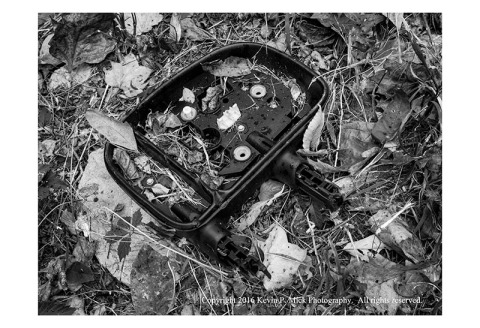 BW photograph of a broken truck mirror laying in fallen leaves.