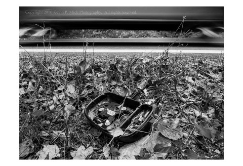 BW photograph of a broken truck mirror laying in fallen leaves with another truck speeding past in the background.