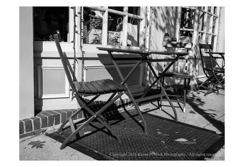 BW photograph of a series of red chairs and tables side lit by direct sun.