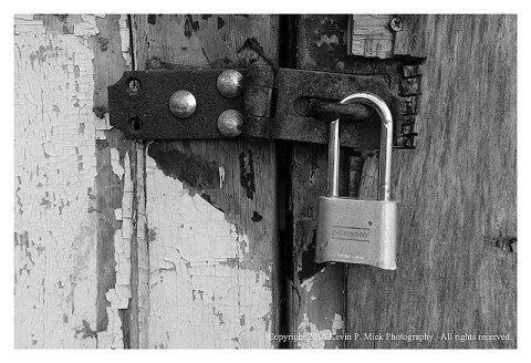 BW photograph of a Master lock on a rusted hasp.