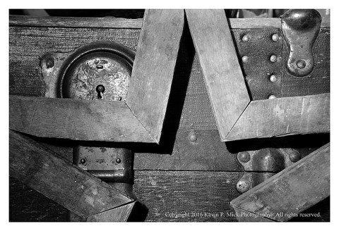BW photograph of a wooden star leaning on an old trunk.