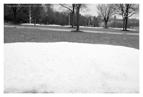 BW photograph of a snow mound in a parking lot with bare trees in the background.