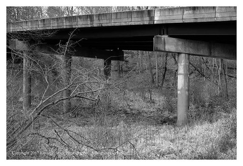 BW photograph of a concrete road overpass overtop a field.