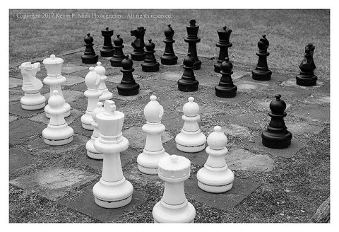 BW photograph of an outdoor chess board's pieces.