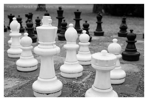BW photograph of a closer view of an outdoor chess board's pieces-emphasis on the white king.