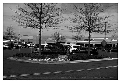 BW photograph of a shopping center's parking lot.