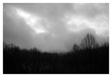 BW photograph of dark clouds over Hog Rock.
